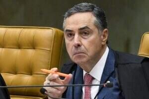 Ministro Roberto Barroso durante sessão do STF, segurando uma caneta de cor laranja