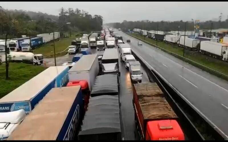 Caminhões parados em via em três filas